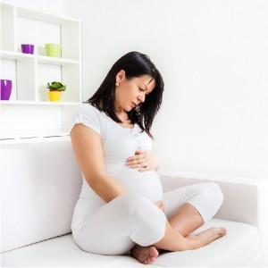 Беременная женщина сидит на кровати