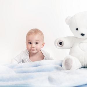 Малыш с белым плюшевым медведем