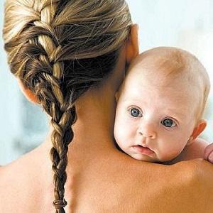 Голова малыша лежит на мамином плече